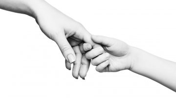 child-hand-holding-mother-finger-on-white-backgrou-VH7GK2J